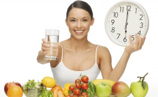 beautiful woman with healthy food water and clock